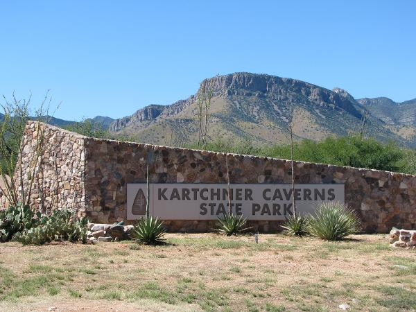 The park sign for Kartchner Caverns State Park with the Whetstone Mountains in the background