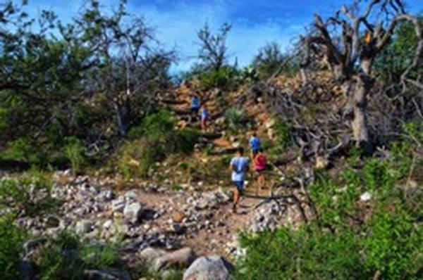 Hikers on the trail at Kartchner Caverns State Park, with the beautiful surroundings.