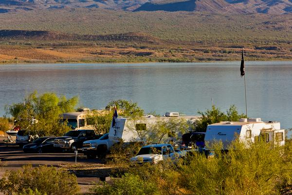 Trucks with campers and boats camp at the side of Alamo Lake State Park, with the expansive lake view behind.