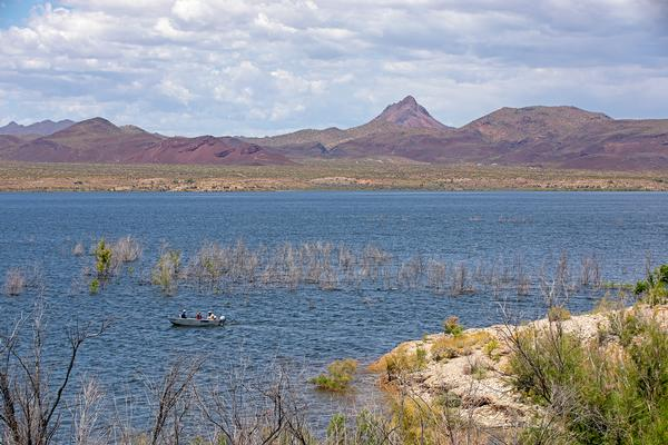 A view across Alamo lake, with mountains in the background and a small fishing boat in the foreground.