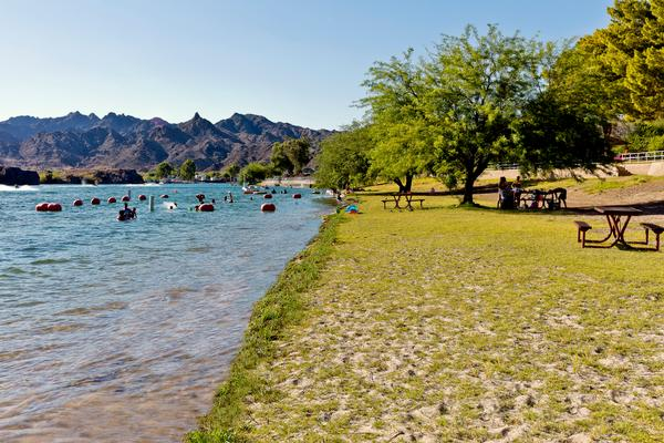 A swimming area with a backdrop of the Buckskin Mountains with tent camping on the shore of the Colorado River
