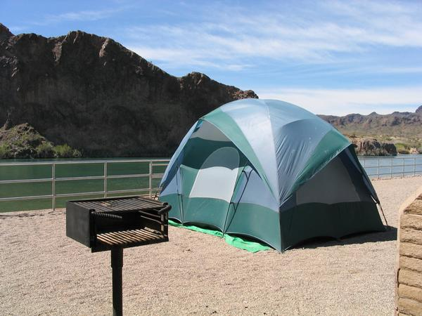 Tent at the water's edge with mountain and Colorado River in the background.