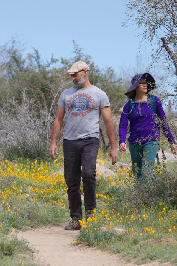Two hikers admire the poppies in Catalina State Park