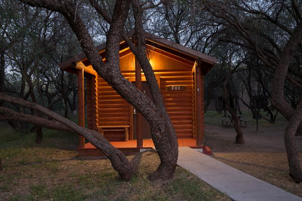 A cabin at Dead Horse Ranch State Park with shade trees and a warm glow.