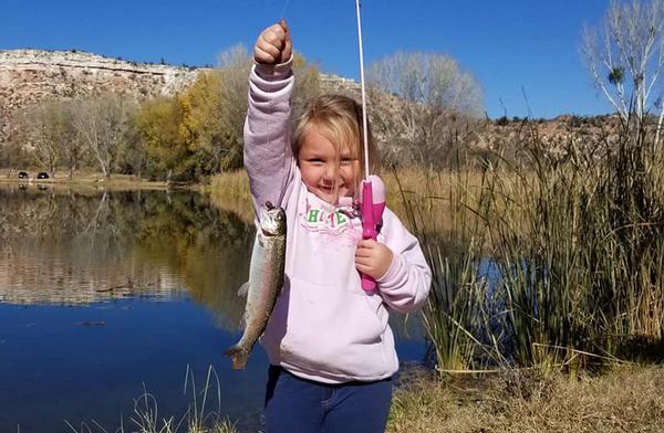A happy angler and her prize