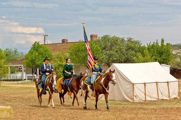 A view of one of the buildings at Fort Verde State Historic Park, with reenactors from Fort Verde Days on horses.