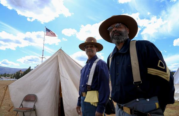 Buffalo Soldier reenactors stand at Fort Verde State Park with the American flag in the backdrop