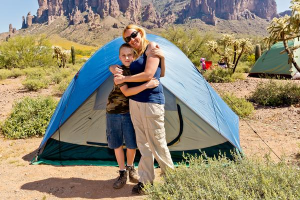 A mother and son hug in front of their tent at Lost Dutchman State Park