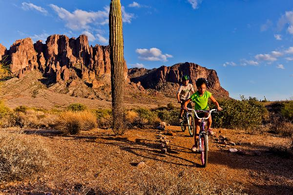 Two kids ride bikes down a trail at Lost Dutchman State Park