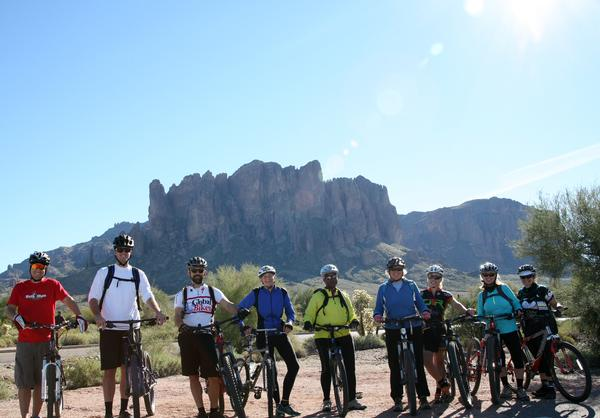 A group of mountain bikers pose in front of the Superstition Mountains at Lost Dutchman State Park.