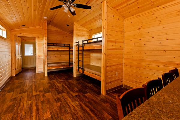 Internal view of the cabin, with warm wood walls, floors and ceiling. Bunk beds to the right, windows and a ceiling fan.