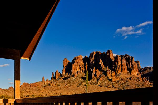The view from the porch of a new cabin at Lost Dutchman State Park. A clear blue sky with the Superstition Mountains in the background. A saguaro cactus stands tall.