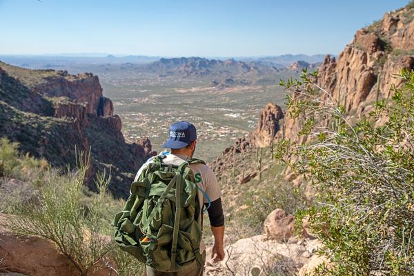 A man hikes down the Flatiron at Lost Dutchman State Park.