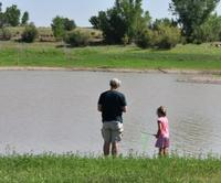A man and child fish at the edge of Lyman Lake State Park
