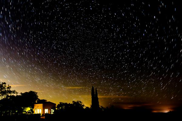 Star trails in the dark night sky over the Kannally Ranch house at Oracle State Park.