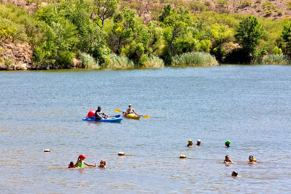 Swimmers and kayakers enjoy Patagonia Lake State Park's blue water lined with shores alive with greenery.
