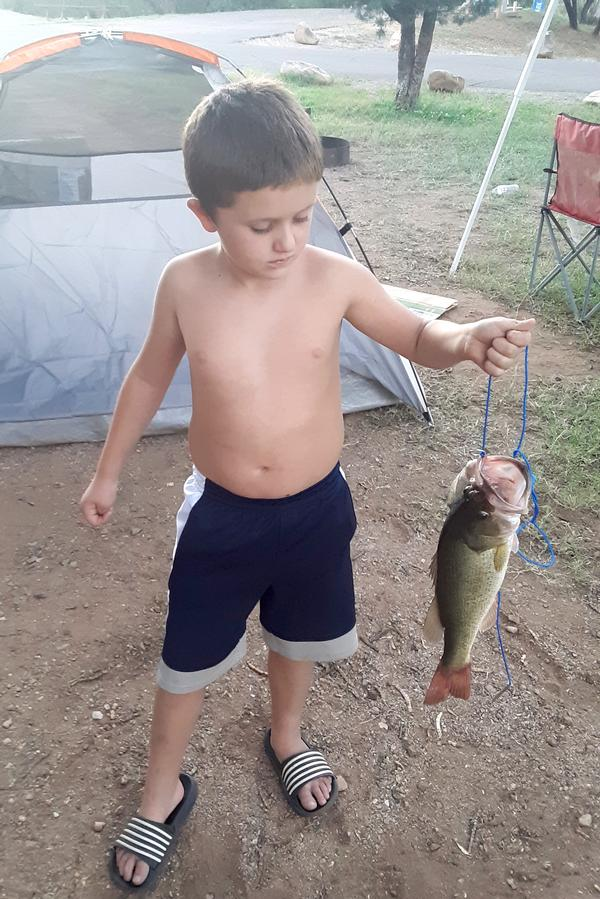 A young boy with his large bass on the hook