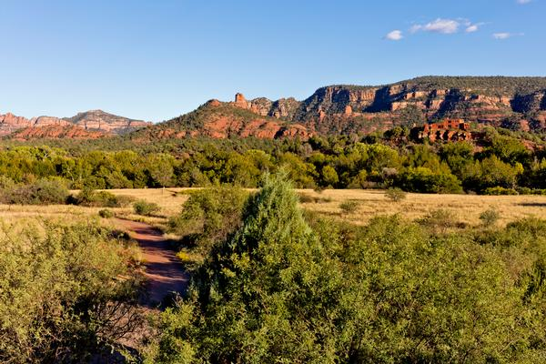 A trail leads into the red rocks with the House of Apache Fires in the distance at Red Rock State Park.