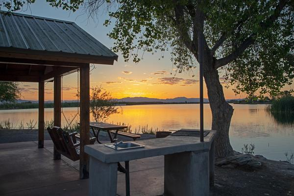A view over Roper Lake from the cabin at the beach at sunset, with porch swing, picnic table, grill and tree.