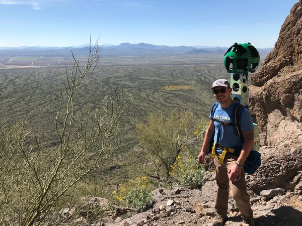 An Arizona State Parks and Trails employee stands with the Google Trekker camera strapped to his back on an overview from Picacho Peak State Park.