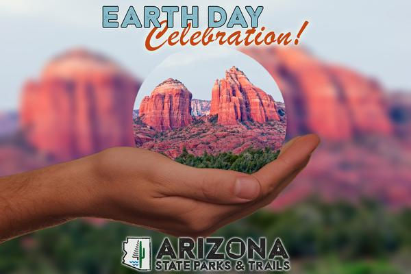 A sphere depicting Red Rock State Park held in the palm of a person's hand. Earth Day Celebration.