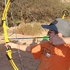 A participant child trying out archery during a family campout weekend